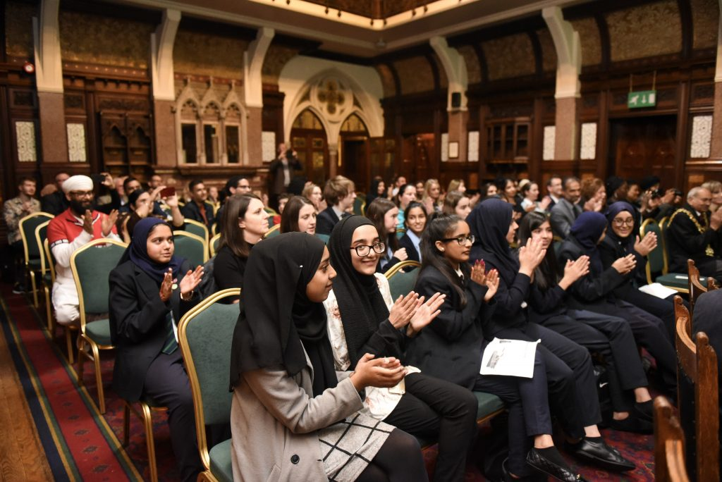 Young school pupils sat in chairs in ornate room, applauding