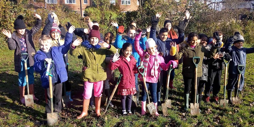 children, parents and staff from World's End Junior School in Quinton helping to plant ten large trees