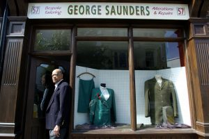 Older man in a tailored suit outside a tailor shop titled 'George Saunders'